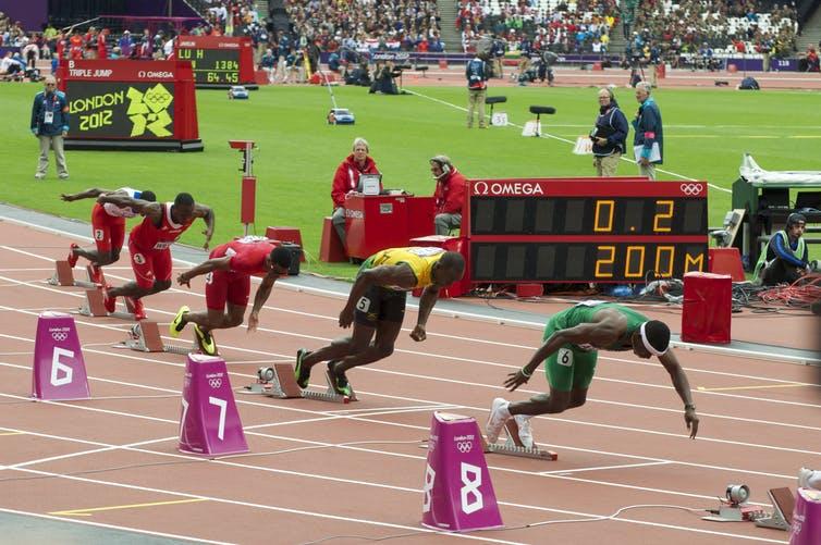Corredores en los tacos de salida de un sprint de 200 m.